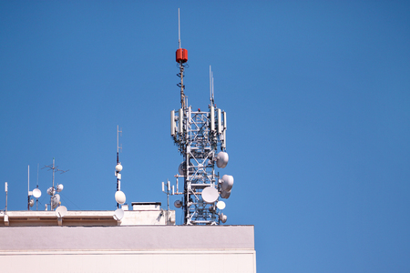 Telecommunication base stations network repeaters on the roof of building. The cellular communication aerial on city building roof. Cell phone telecommunication tower. Antennas on top of building. Stock Photo
