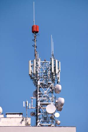 Telecommunication network repeaters, base transceiver station. Tower wireless communication antenna transmitter and repeater. Telecommunication tower with antennas. Cell phone telecommunication tower. Фото со стока