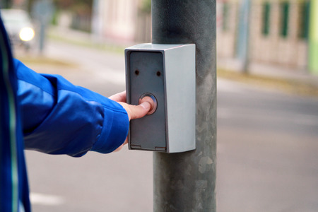 Portrait of male hand pressing button for crossing street on crosswalk and traffic light Stock Photo
