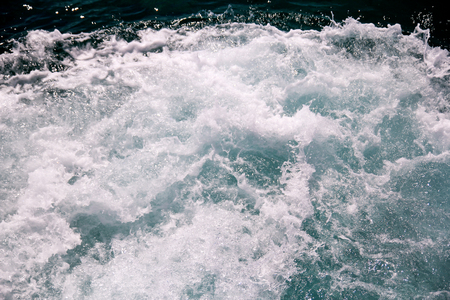 Turbulence made by foam of sea water from a high-speed yacht on surface of sea.