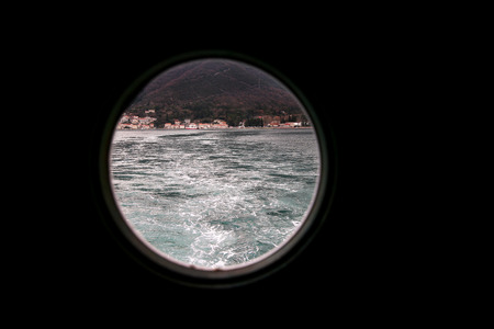 Hinged round window, storm cover on ship looking outside into Mediterranean sea. Porthole view through window on ship to turbulence made by foam of sea water from a high-speed boat on surface of sea.