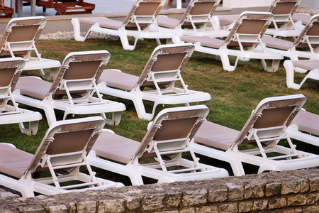 Exotic beach on mediterranean sea, sunbeds for sunbathing and relax on grass in tropical garden of luxury resort hotel. Sun loungers on lawn waiting for tourists. Idyllic seaside in summer season.