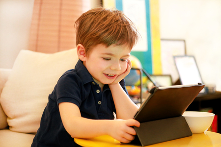Child using tablet pc on bed at home. Stock Photo
