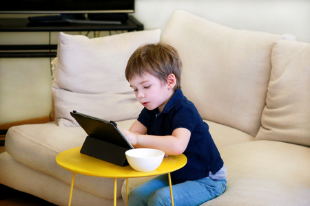 Child using tablet pc on bed at home. Cute boy on sofa is watching cartoon, playing games and learning from laptop.