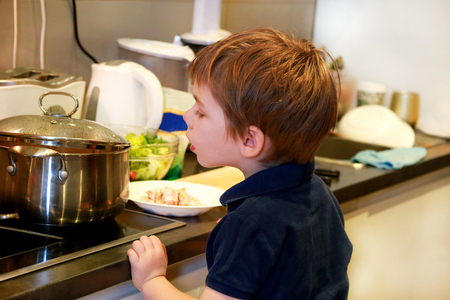 Portrait of child in kitchen. Cute little boy, playing in kitchen. Stock Photo