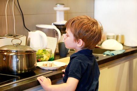 Portrait of child in kitchen. Cute little boy, playing in kitchen