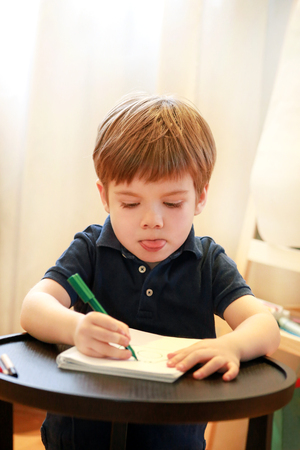 Child is drawing and painting with felt pen on paper of spiral notebook on small wooden table in living room at home.