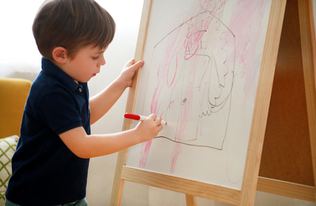 Child is drawing and painting with felt pen on paper of wooden drawing board artist easel for kids and children at home.