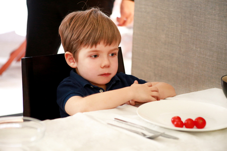 Hungry child sitting in chair at table in kitchen and waiting for meal and lunch.