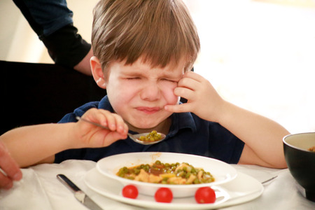 Hungry child sitting in chair at table in kitchen and despises, disapproves of hot meal, because he does not like lunch.