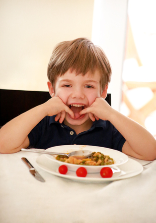 Hungry child sitting in chair at table in kitchen and eating with spoon of cooked peas with tomato. Stock Photo