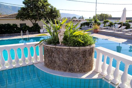 Corfu city, Greece - July 29, 2017: Swimming pool of luxury holiday villa. Relax near exotic swimming pool with handrail, deck chairs, sun loungers waiting for tourists in tropical resort hotel.