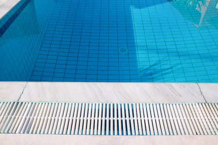 Blue ripped water in swimming pool in tropical resort with edge of pavement. Stock Photo