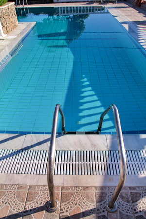 Handrail on pool. Swimming pool with stair at tropical resort.