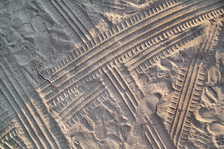 Tracks in sand. Part of prints and tracks of tire, foot, feet, sun sea slippers in beach sand. Banque d'images
