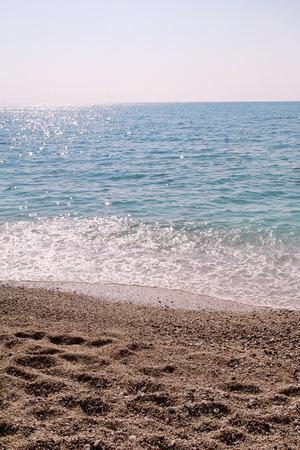 Exotic sandy beach, tropical blue mediterranean sea with waves and sea foam.