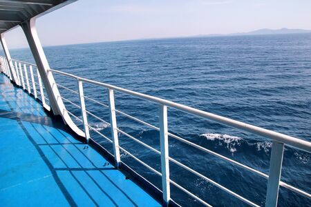 Details of passenger boat. Cruise ship deck. Picturesque view from ship deck on navy blue sea, horizon and sky during vacation trip by cruiser. Balcony with sea or ocean view exterior of ship or boat.