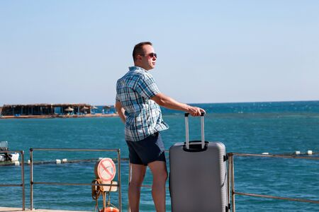 Tourist and traveler is stand on beach of hotel resort with traveled suitcase