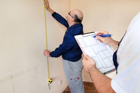 Ingegnere, appaltatore e project manager con il suo collega, operaio edile, tuttofare e costruttore sta misurando la parete della stanza per la ristrutturazione utilizzando un metro a nastro e controllando il progetto dell'appartamento.