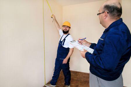 L'ingénieur, l'entrepreneur et le chef de projet avec son collègue, ouvrier du bâtiment, bricoleur et constructeur mesurent le mur de la pièce à rénover à l'aide d'un ruban à mesurer et vérifient le plan de l'appartement.
