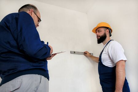 Engineer, contractor and project manager with his colleague, construction worker, handyman and builder is measuring wall room for renovation using spirit level tool, checking in apartment blueprint. Stockfoto