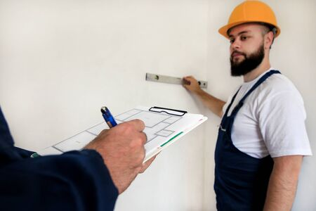 Engineer, contractor and project manager with his colleague, construction worker, handyman and builder is measuring wall room for renovation using spirit level tool, checking in apartment blueprint. Banque d'images