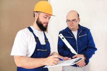 L'ingénieur, l'entrepreneur et le chef de projet avec son collègue, ouvrier du bâtiment, bricoleur et constructeur mesurent la pièce murale à rénover à l'aide d'un outil de niveau à bulle, vérifiant le plan de l'appartement. Banque d'images