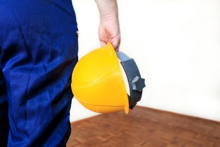 Construction worker and handyman is working on renovation of apartment. Builder at construction site with protective uniform and equipment, he with suit, coverall and yellow helmet holding in hand. Banque d'images - 130736502