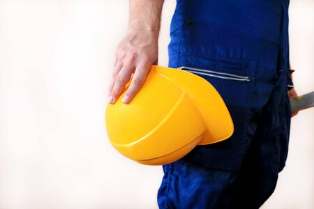 Construction worker and handyman is working on renovation of apartment. Builder at construction site with protective uniform and equipment, he with suit, coverall and yellow helmet holding in hand. Banque d'images - 130736505