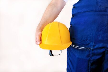 Construction worker and handyman is working on renovation of apartment. Builder at construction site with protective uniform and equipment, he with suit, coverall and yellow helmet holding in hand. Stock Photo