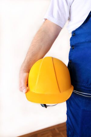 Construction worker and handyman is working on renovation of apartment. Builder at construction site with protective uniform and equipment, he with suit, coverall and yellow helmet holding in hand. Banque d'images - 130736514