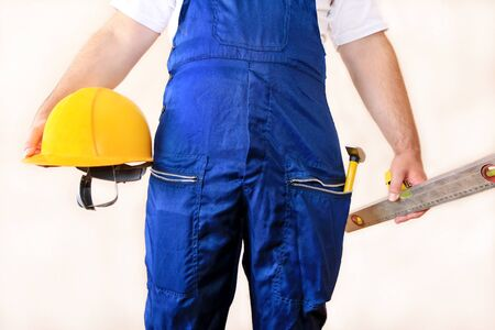 Construction worker at construction site with protective uniform, construction service tools and equipment, coverall and holds yellow helmet, hammer tool, measure tape, spirit level tool in hands. Foto de archivo - 130736720