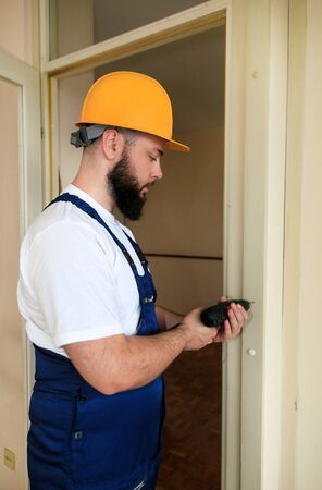 Construction worker and handyman works on renovation of apartment.