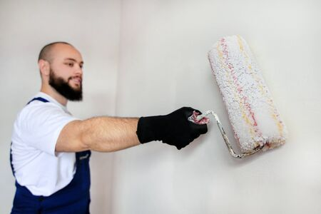 Construction worker doing finish renovation at apartment. Professional painter contractor using white paint roller brush painting of concrete wall room on construction site. Home renovation concept. Standard-Bild