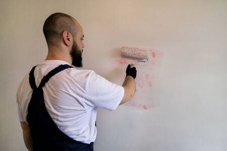 Construction worker doing finish renovation at apartment. Professional painter contractor using white paint roller brush painting of concrete wall room on construction site. Home renovation concept. Stockfoto