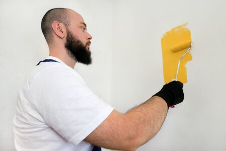 Construction worker and handyman doing finish renovation at apartment. Professional painter using paint roller brush painting of wall with yellow color on construction site. Home renovation concept.