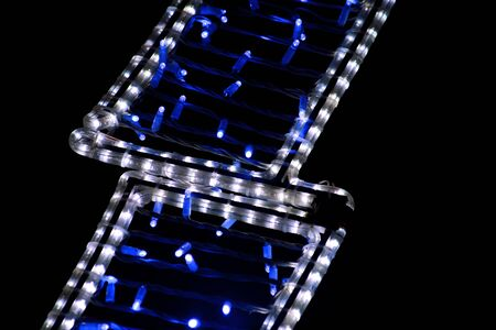 Part of Christmas decorative blue and white flashing lights, close up.