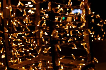 Part of Christmas decorative yellow, golden, white flashing lights, close up. Reklamní fotografie - 135466420