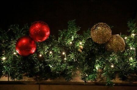 Traditional decorated Christmas baubles on wreath made of green fir or spruce branches and glowing garland outdoors. Twigs pine, red and gold Christmas balls as decorations for New Year holidays. Reklamní fotografie