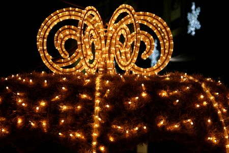 Modern decorative holiday pipes with yellow flashing lights lamps in shape of Christmas decoration, close up. Banco de Imagens