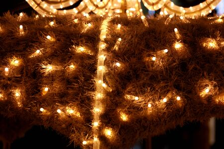 Part of Christmas decorative yellow and white flashing lights, close up. Detail of New Year and Christmas decorations, string rice lights bulbs. Ornaments to christmas celebration, holiday scene.
