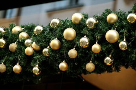 Traditional decorated Christmas baubles on wreath made of green fir or spruce branches and glowing garland outdoors. Twigs pine, gold and silver Christmas balls as decorations for New Year holidays. Stock Photo