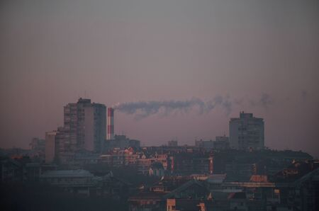 Smoking from industrial chimneys of heating plant emits smoke, smog at sunrise in city, pollutants enter atmosphere. Environmental disaster. Harmful emissions, exhaust gases into air. Heating season. Stock Photo