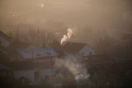 Smoking chimneys at roofs of houses emits smoke, smog at sunrise, pollutants enter atmosphere. Environmental disaster. Harmful emissions and exhaust gases into air. Fog, winter day, heating season. Reklamní fotografie