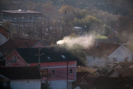 Smoking chimneys at roofs of houses emits smoke, smog at sunrise, pollutants enter atmosphere. Environmental disaster. Harmful emissions and exhaust gases into air. Fog, winter day, heating season. Stock Photo