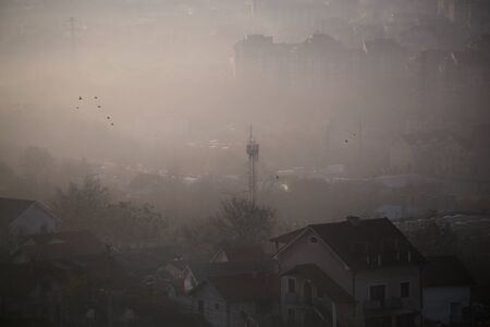Winter morning view on landscape of houses, buildings and telecommunication tower with fog. Environmental disaster. Harmful emissions and exhaust gases into air. Winter day, weather, heating season.