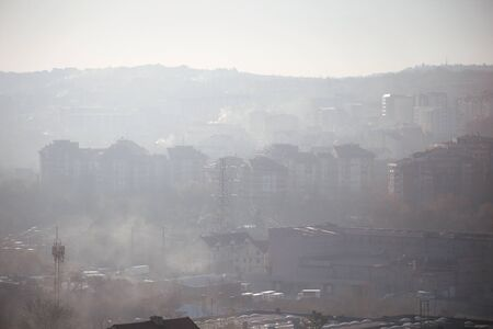 Winter morning atmosphere view on landscape of houses and buildings with fog covered street. Environmental disaster. Harmful emissions and exhaust gases into air. Winter day, weather, heating season.