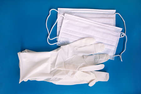 Medical protective disposable white masks and glove on blue background. Protection equipment against virus, flu and coronavirus (COVID-19), bacterial and germs. Health care and surgical concept.