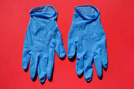 Pair of medical blue latex protective gloves on red background. Protective disposable gloves against the spread of virus, flu, coronavirus (COVID-19), bacterial. Health care and surgical concept. Stock Photo