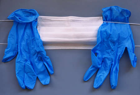 Pair of medical blue latex protective glove and white mask on gray background. Protection equipment against virus, flu, coronavirus (COVID-19), bacterial and germs. Health care and surgical concept.